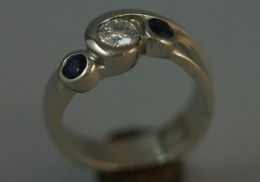 14kt. white gold engagement ring with diamond and natural blue sapphires.